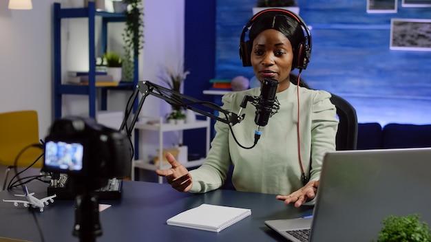 Portret afrykańskiej blogerki rozmawiającej z publicznością patrzącą na profesjonalną kamerę wideo pracującą w domowym studiu podcastów