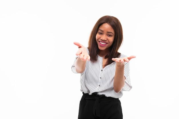 Portret afrykańskiej młodej dziewczyny possing i gestykuluje ręce na tle