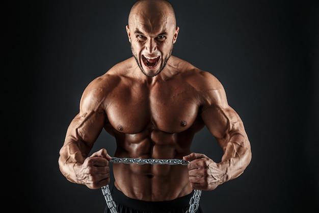 Portret agresywnego kulturysty próbującego oderwać metalowy łańcuch