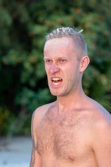 Portret agresywnego młodzieńca z dredami na głowie w przyrodzie na tropikalnej plaży, zbliżenie