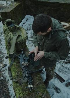 Portret airsoftowca w profesjonalnym sprzęcie ładuje broń nabojami w lesie. żołnierz z bronią na wojnie
