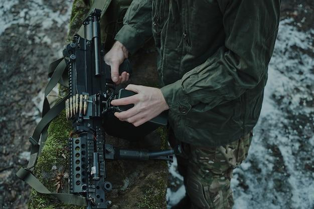 Portret airsoftowca w profesjonalnym sprzęcie ładuje broń z nabojami w lesie. żołnierz z bronią na wojnie