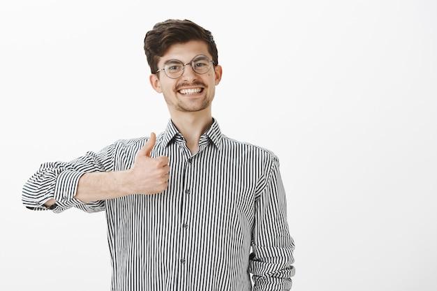 Portret aktywnego i pozytywnie nastawionego współpracownika w okrągłych okularach, uśmiechającego się radośnie, pokazującego kciuki do góry, gotowego do każdej pracy, wyrażającego aprobatę i mówiącego, że lubi pomysły na szarej ścianie