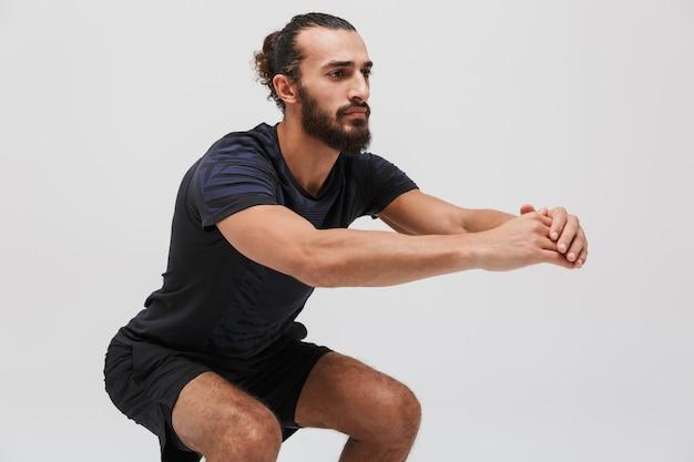 Portret aktywnego sportowca brunetki noszącego dres robi trening na białym tle