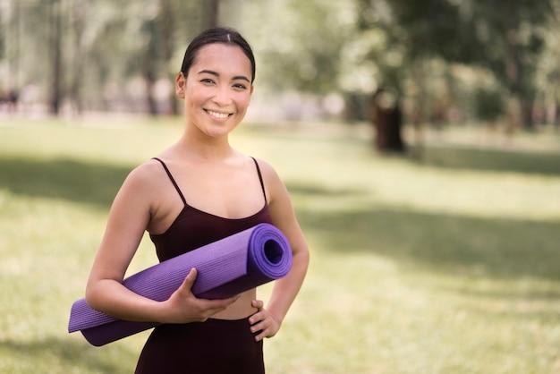 Portret aktywnej kobiety mienia joga mata