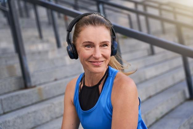 Portret aktywnej kobiety w średnim wieku w odzieży sportowej i słuchawkach uśmiecha się do kamery pozowanie na zewnątrz