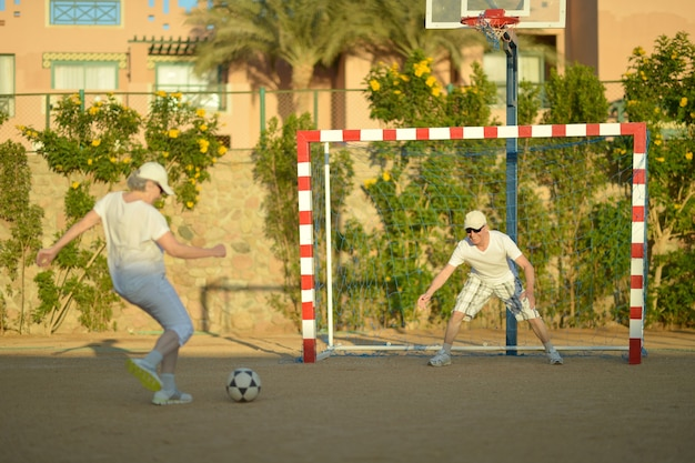 Portret aktywnej pary seniorów grającej w piłkę nożną