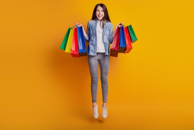 Portret aktywnej pozytywnej dziewczyny skaczącej, trzymającej okazje na zakupy izolowane na żółtym tle