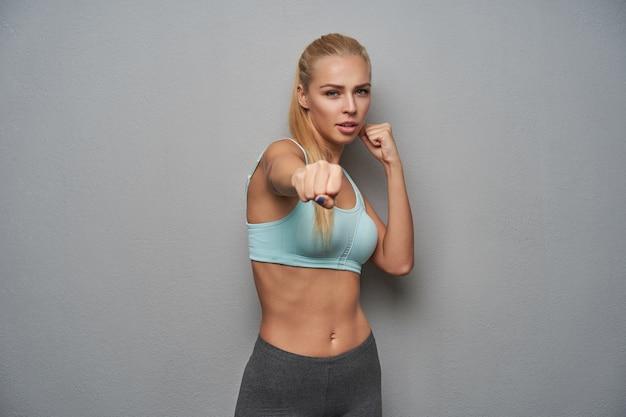 Portret aktywnej, szczupłej młodej kobiety o długich blond włosach, patrzących groźnie na aparat i unoszących pięści, gotowa do walki, stojąca na jasnoszarym tle w sportowych ubraniach