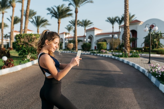 Portret aktywny szczęśliwy sportsmenka dokonywanie selfie na ulicy w tropikalnym mieście. słoneczny poranek, wesoły nastrój, motywacja, trening, uśmiech, zdrowy tryb życia, fitness, atrakcyjna modelka.