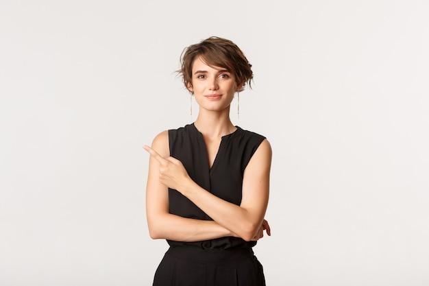 Portret ambitnej uśmiechnięta młoda kobieta, wskazując lewy górny róg i pokazując transparent, biały.