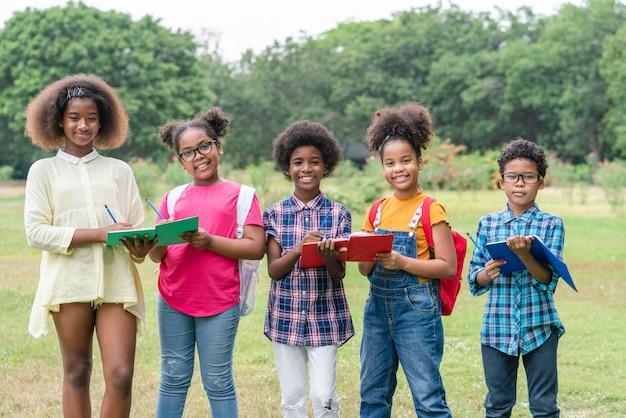 Portret amerykan afrykańskiego pochodzenia children trzyma książki i patrzeje kamerę podczas gdy stojący w parku szkoła
