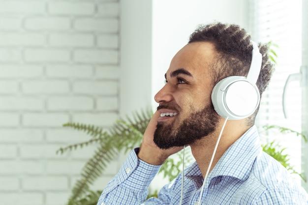 Portret amerykanina afrykańskiego pochodzenia młody człowiek słucha muzyka w hełmofonach