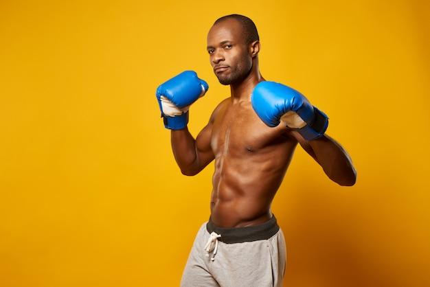 Portret amerykanina afrykańskiego pochodzenia sportowy bokser w błękitnych rękawiczkach.