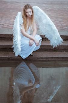 Portret anioła dziewczyna siedzi w pobliżu wody i patrzy na jej odbicie