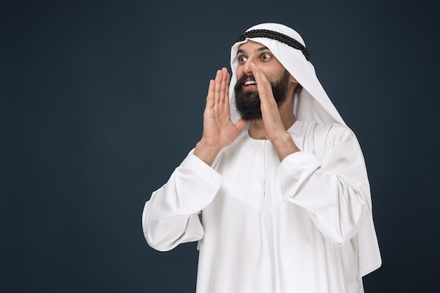 Portret arabski saudyjski biznesmen na ciemnoniebieskim