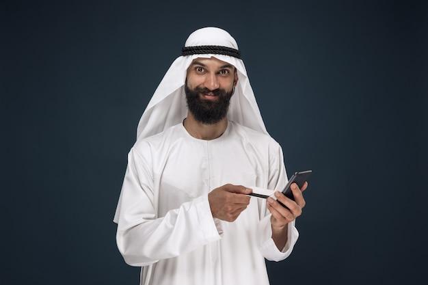Portret arabski saudyjski biznesmen na ciemnym niebieskim tle studio. mężczyzna za pomocą smartfona do płacenia rachunków, zakupów online lub zakładów. pojęcie biznesu, finanse, wyraz twarzy, ludzkie emocje.