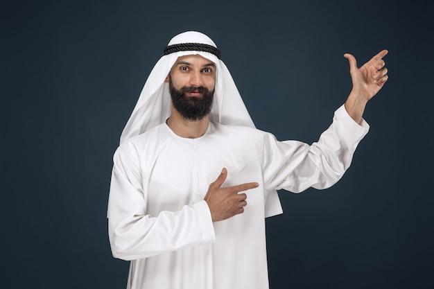 Portret arabskiego mężczyzny saudyjskiego. młody mężczyzna model uśmiecha się i wskazuje.