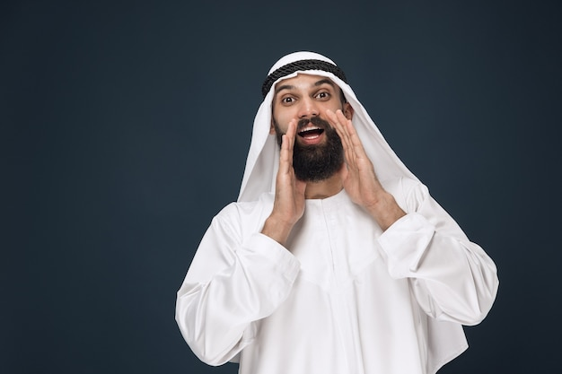 Portret arabskiego saudyjskiego biznesmena na ciemnoniebieskiej ścianie studio