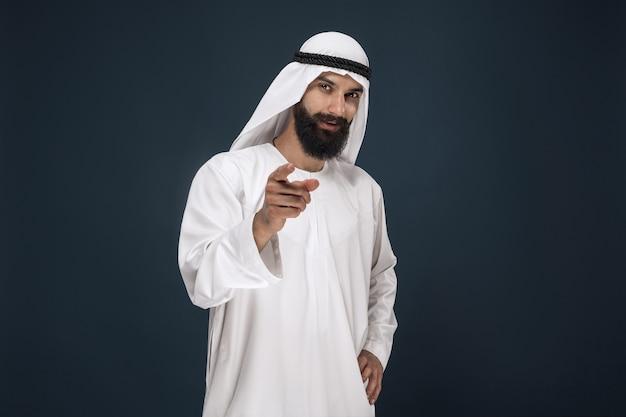 Portret arabskiego szejka saudyjskiego. młody mężczyzna model uśmiecha się i wskazuje lub wybiera.