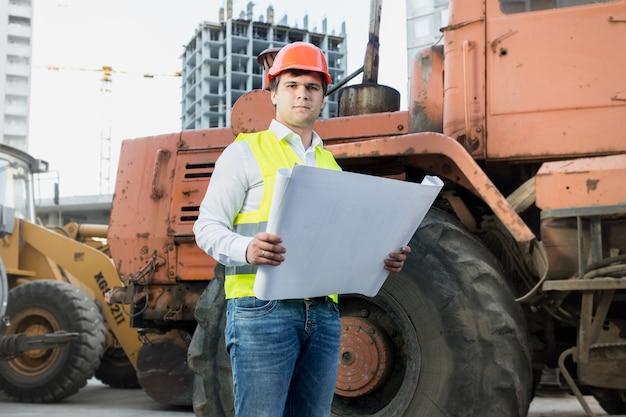 Portret architekta czytającego plany obok buldożera na placu budowy