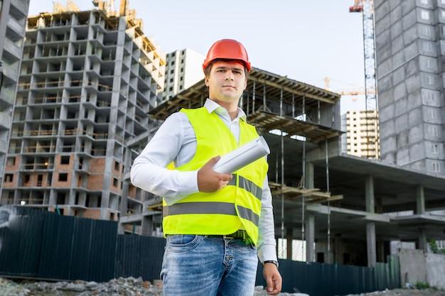 Portret architekta w czerwonym kasku pozowanie na placu budowy