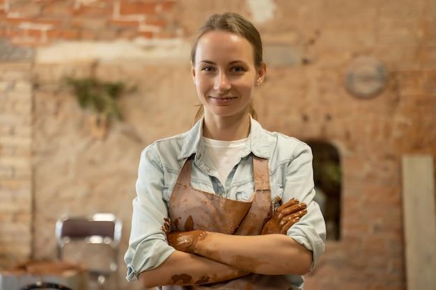 Portret artystki ceramiki w jej pracowni artystycznej kobieta garncarka w fartuchu krzyżuje ramiona i patrzy w kamerę