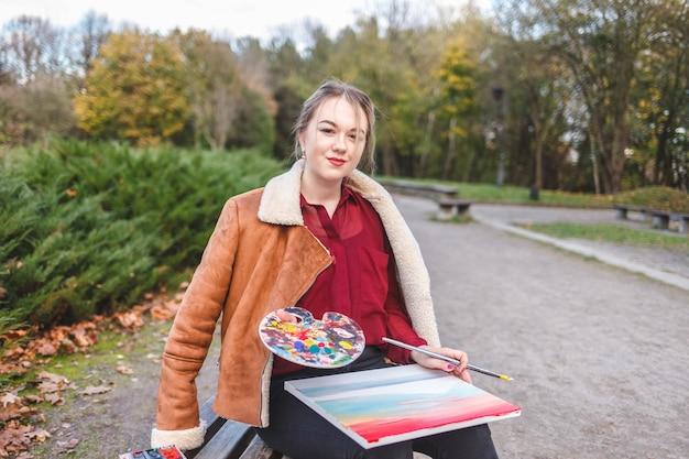 Portret artysty ulicznego, który siedzi w parku na ławce i trzyma w rękach obraz, paletę i pędzel