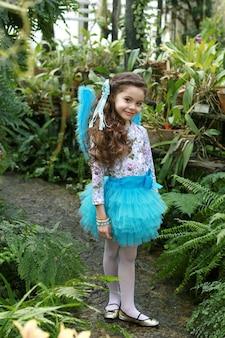 Portret artystyczny długowłosej dziewczyny w romantycznej sukience z anielskimi skrzydłami