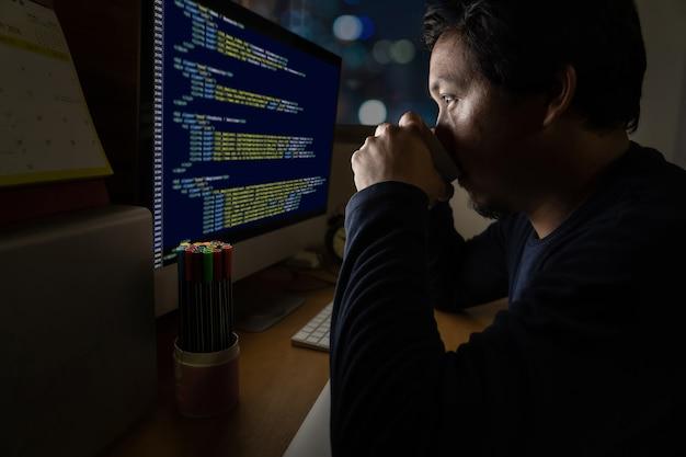 Portret asia biznesmena obsiadanie i działanie mocno na stole z programowania źródłem
