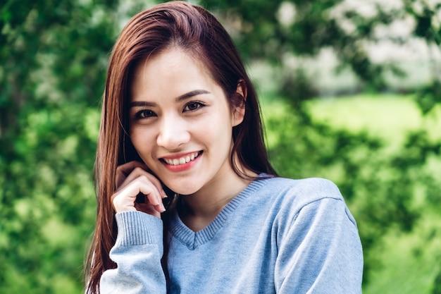 Portret asia kobieta cieszy się i relaksuje na zielonej natury ścianie azjatycki piękno