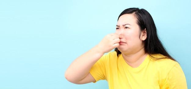 Portret asia kobieta czuje się nieczysto, na niebieskim tle w studio
