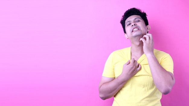 Portret asia mężczyzna chrobota szyja i dokuczliwy świąd na różowym tle w studiu