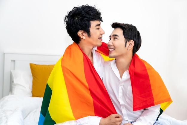 Portret asian para homoseksualnych przytulić i trzymając rękę z flagą dumy w sypialni. koncepcja gejów lgbt.