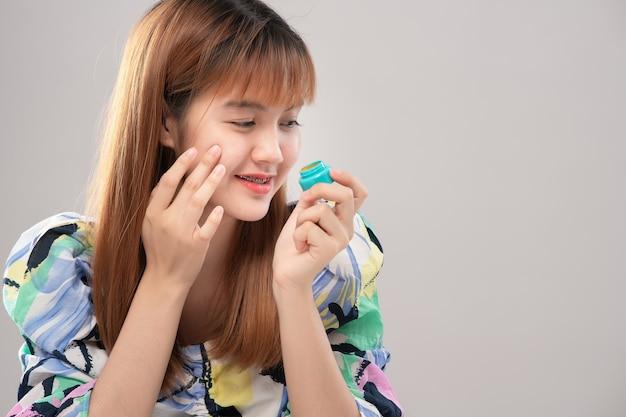Portret asian piękna kobieta przedstawia krem do twarzy; perfekcja odmładzanie rewitalizacja koncepcja nawilżania i pielęgnacji skóry. model pokazujący produkt kosmetyczny pod ręką