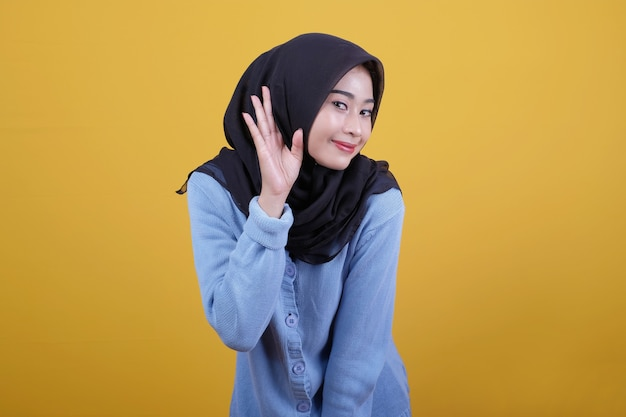 Portret asian piękna kobieta ubrana w czarny hidżab, słysząc coś espression