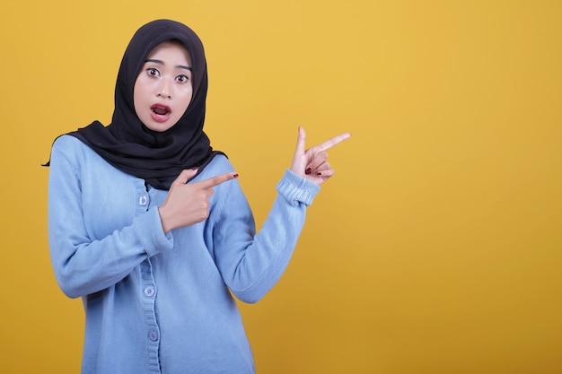 Portret asian piękna kobieta ubrana w czarny hidżab, zaskoczony wyraz wskazujący palcem wskazującym