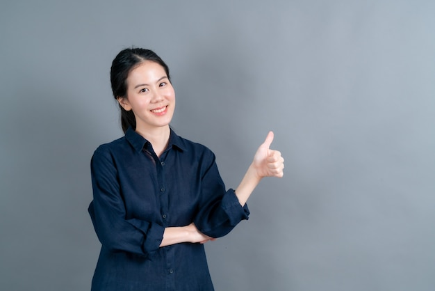 Portret asian piękna młoda kobieta stojąca, zrobiła kciuki do góry na szarej ścianie