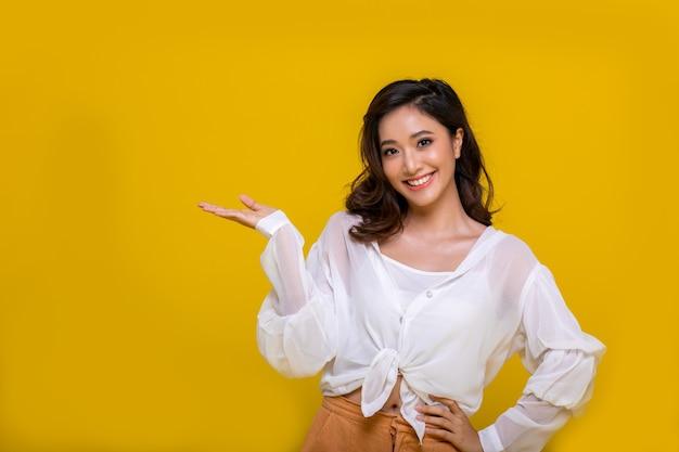Portret asian piękna szczęśliwa młoda kobieta uśmiechnięta wesoła i patrząc na kamery na białym tle na żółtym tle studio