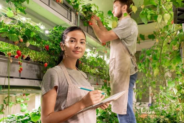 Portret asystenta cieplarnianego rasy mieszanej, który robi notatki w schowku podczas pracy z hodowcą
