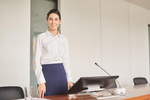 Portret asystentka uśmiecha się do kamery, stojąc w pustej sali konferencyjnej