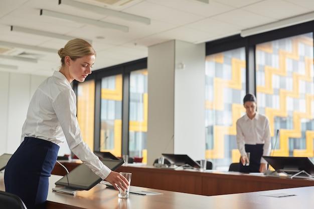 Portret asystentki stawiającej szklankę wody na stole podczas przygotowywania sali konferencyjnej na wydarzenie biznesowe,