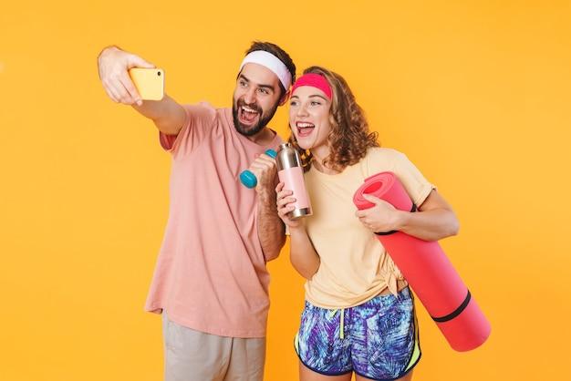Portret atletycznej młodej pary szczęśliwej biorącej zdjęcie selfie z hantlami i matą fitness na białym tle nad żółtą ścianą