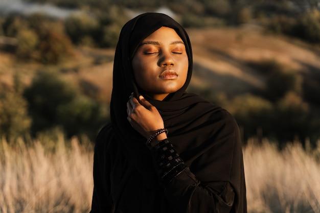 Portret atrakcyjna afrykańska dziewczyna w czarnej tradycyjnej szacie. salah modli się w bogu.