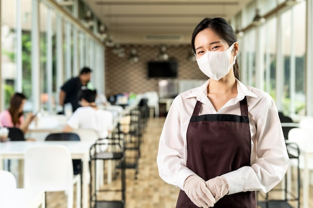 Portret atrakcyjna azjatycka kelnerka nosić twarz z klientami w społecznej odległości
