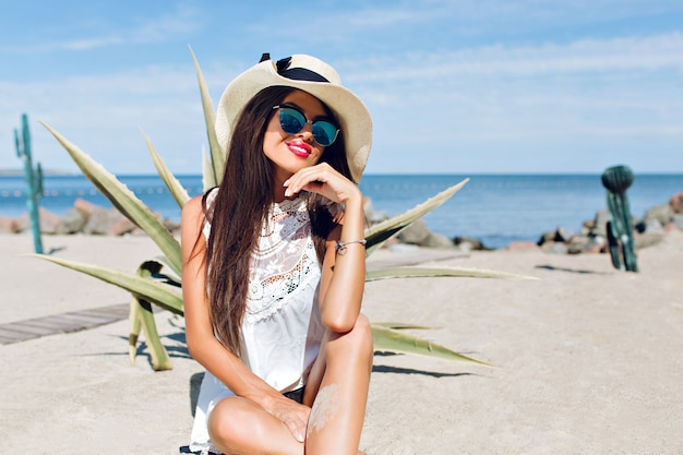 Portret atrakcyjna brunetka dziewczyna z długimi włosami, siedząc na plaży w pobliżu kaktusa na tle. ona uśmiecha się do kamery.