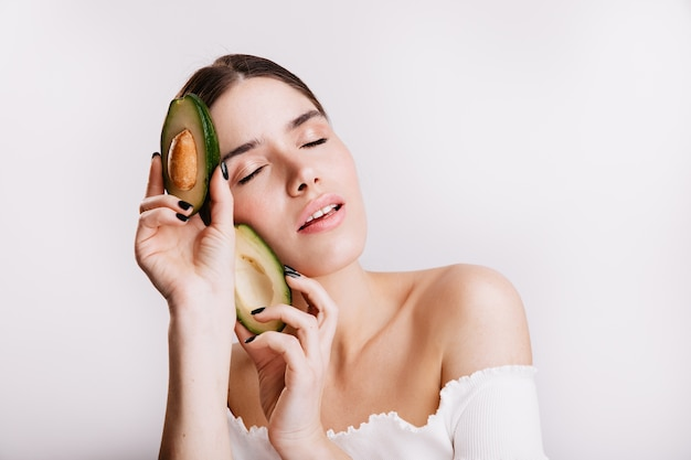 Portret atrakcyjna brunetka dziewczyna z lekką czystą skórą. kobieta pozuje z zamkniętymi oczami, trzymając awokado na białej ścianie.