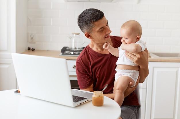 Portret atrakcyjna brunetka mężczyzna freelancer ubrany w bordową koszulkę w stylu casual, pracująca i opiekująca się swoją małą córeczką, patrząc na dziecko z miłością.