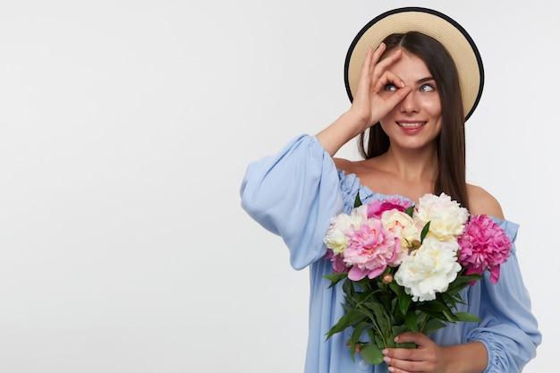 Portret atrakcyjna dziewczyna z długimi brunetkami. w kapeluszu i niebieskiej sukience. trzymając bukiet pięknych kwiatów i obserwując palcami w lewo w miejsce kopiowania nad białą ścianą