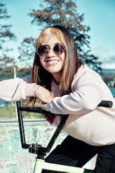 Portret atrakcyjna dziewczyna z długimi włosami i okularami przeciwsłonecznymi oparty na jej rowerze